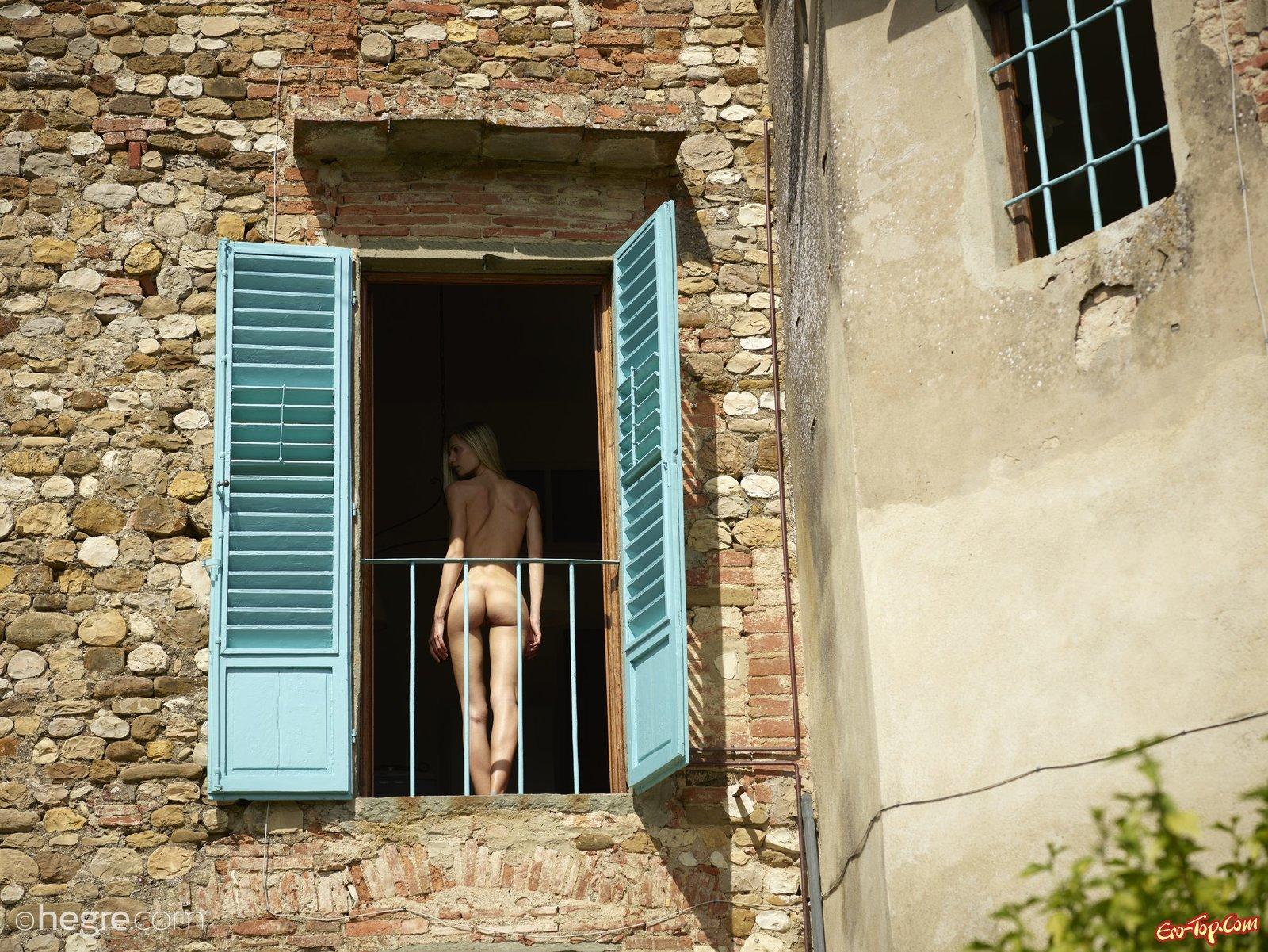 Раздетая светлая порноактриса фоткается стоя у открытого окошка