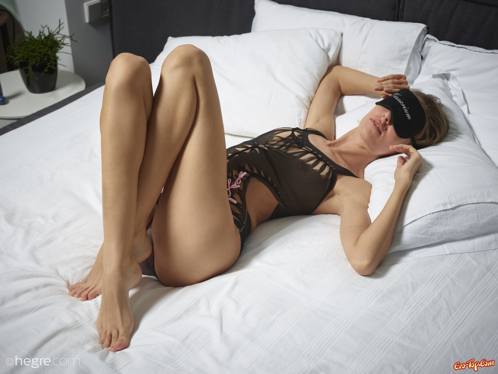 Худая мадам в эротическом белье фотографируется на лежанке
