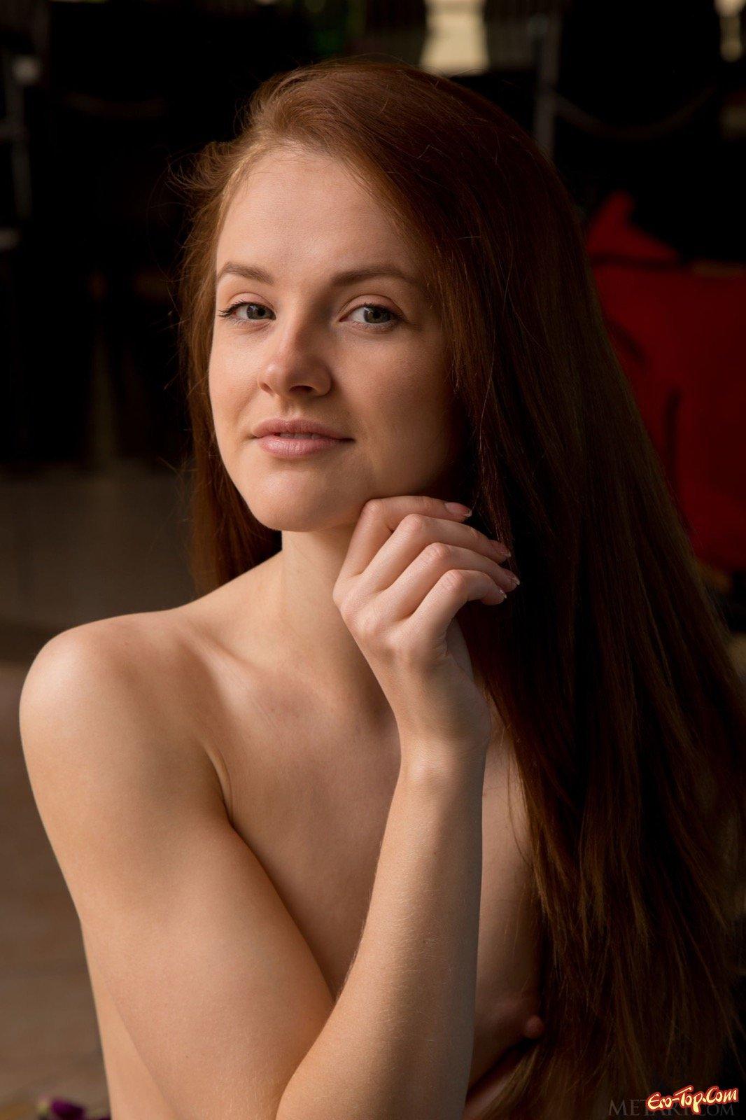 Рыжая девушка оголила маленькую грудь на диване