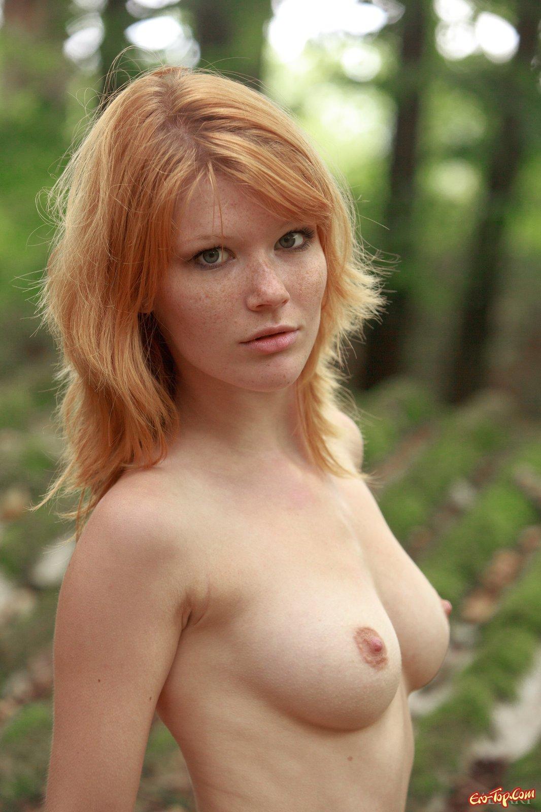 Роскошная рыженькая баба фотографируется на крыше в лесу