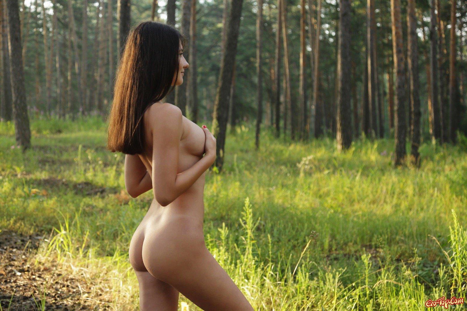 Симпатичная девушка снимает шортики и майку в лесу