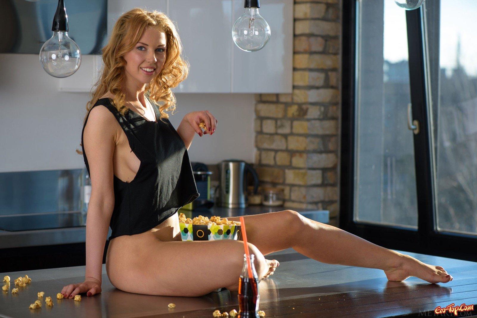 Кудрявая блондинка разделась и делает селфи на столике