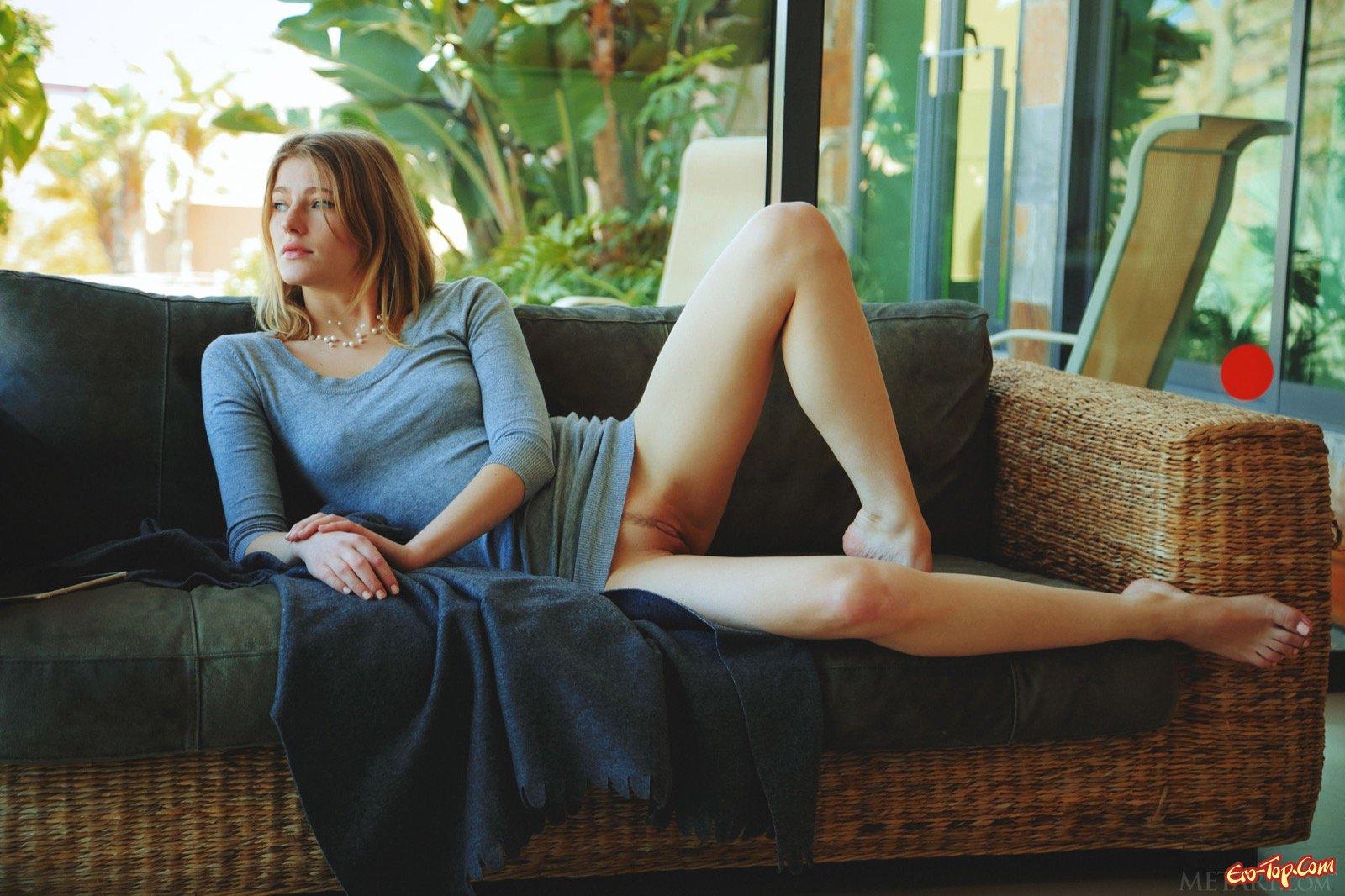 Блондинка снимает платье и позирует лежа на диване