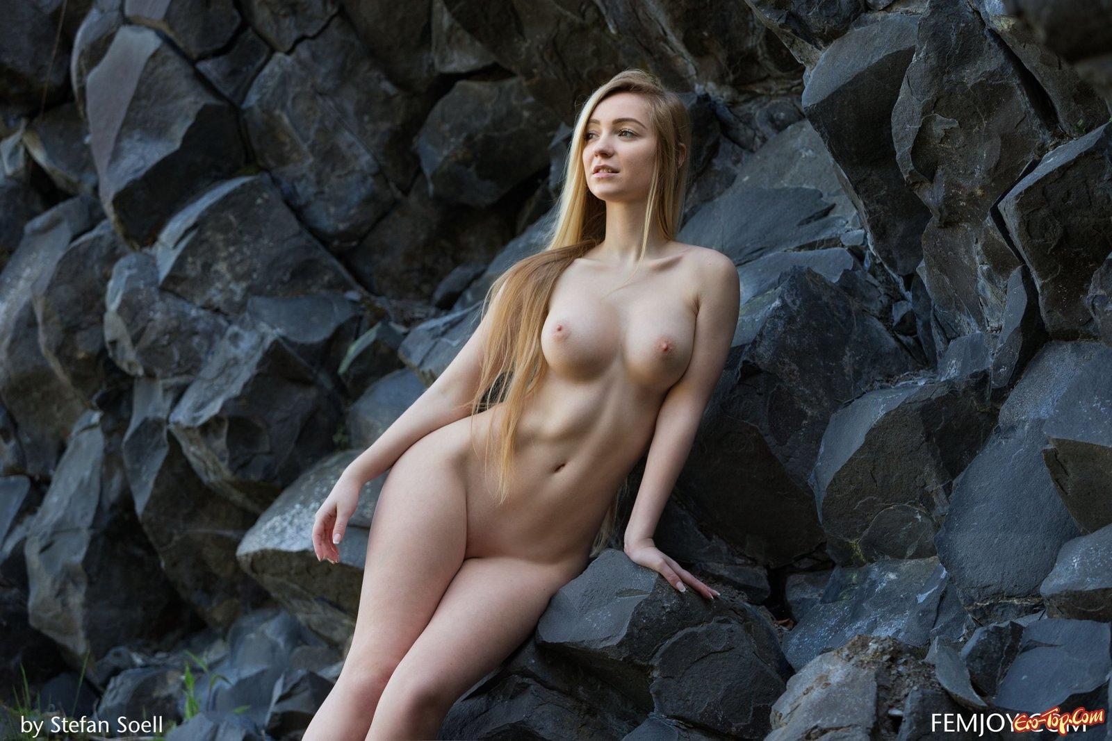 Стройная грудастая блондинка позирует у скалы
