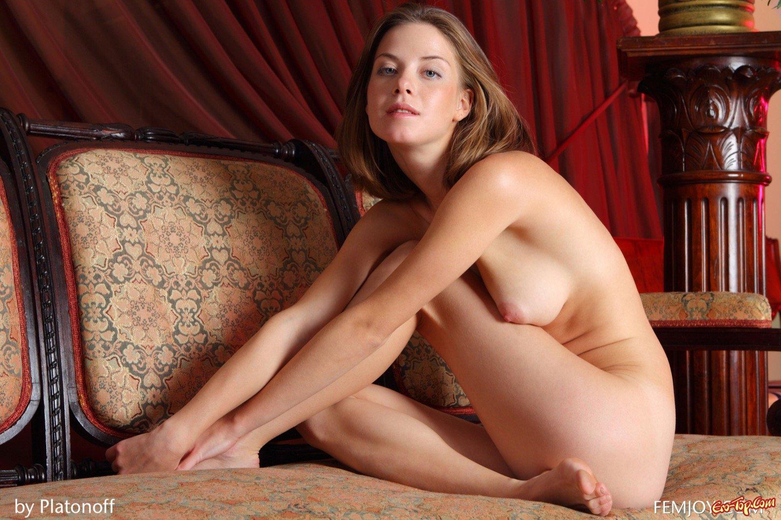 Голая девушка принимает эротичные позы на диване