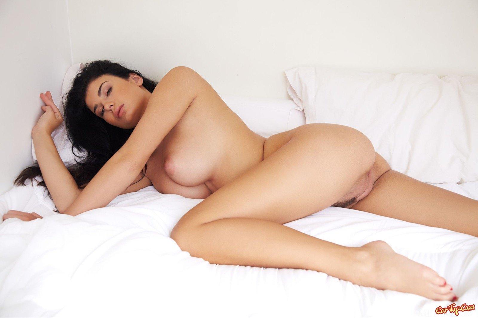 Брюнетка с крупными сиськами позирует в постели