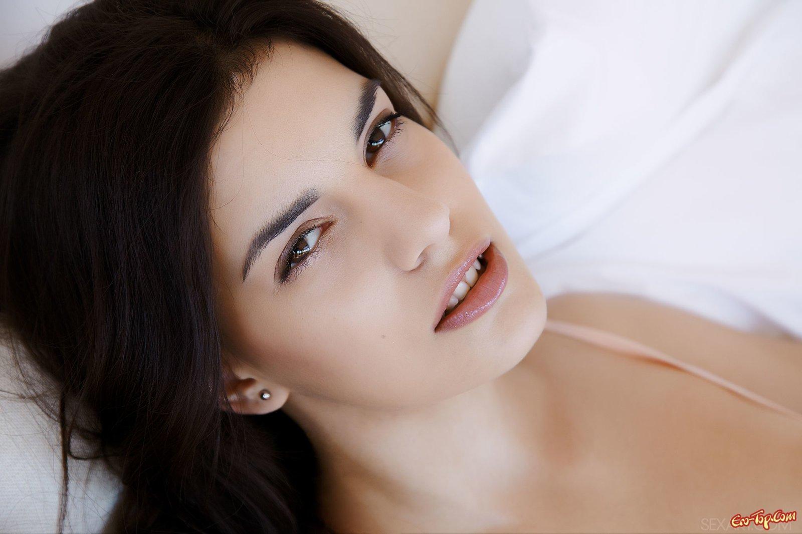 Брюнетка лежит в постели и эротично стягивает трусики