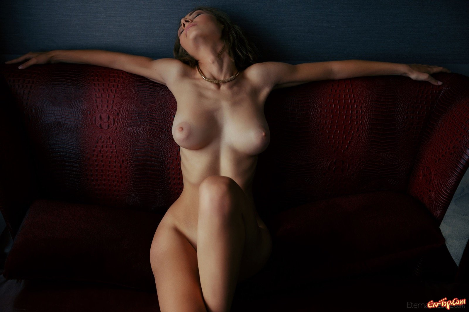 Стройная девушка с большой грудью позирует на диване