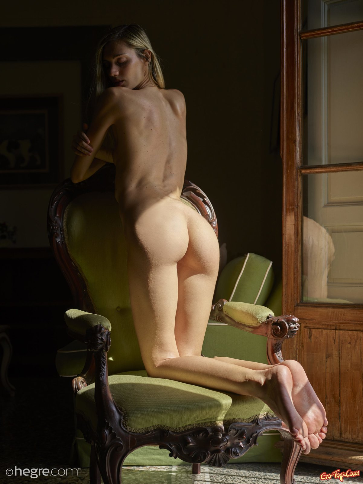 Тощая голая девушка почти без сисек позирует у окна