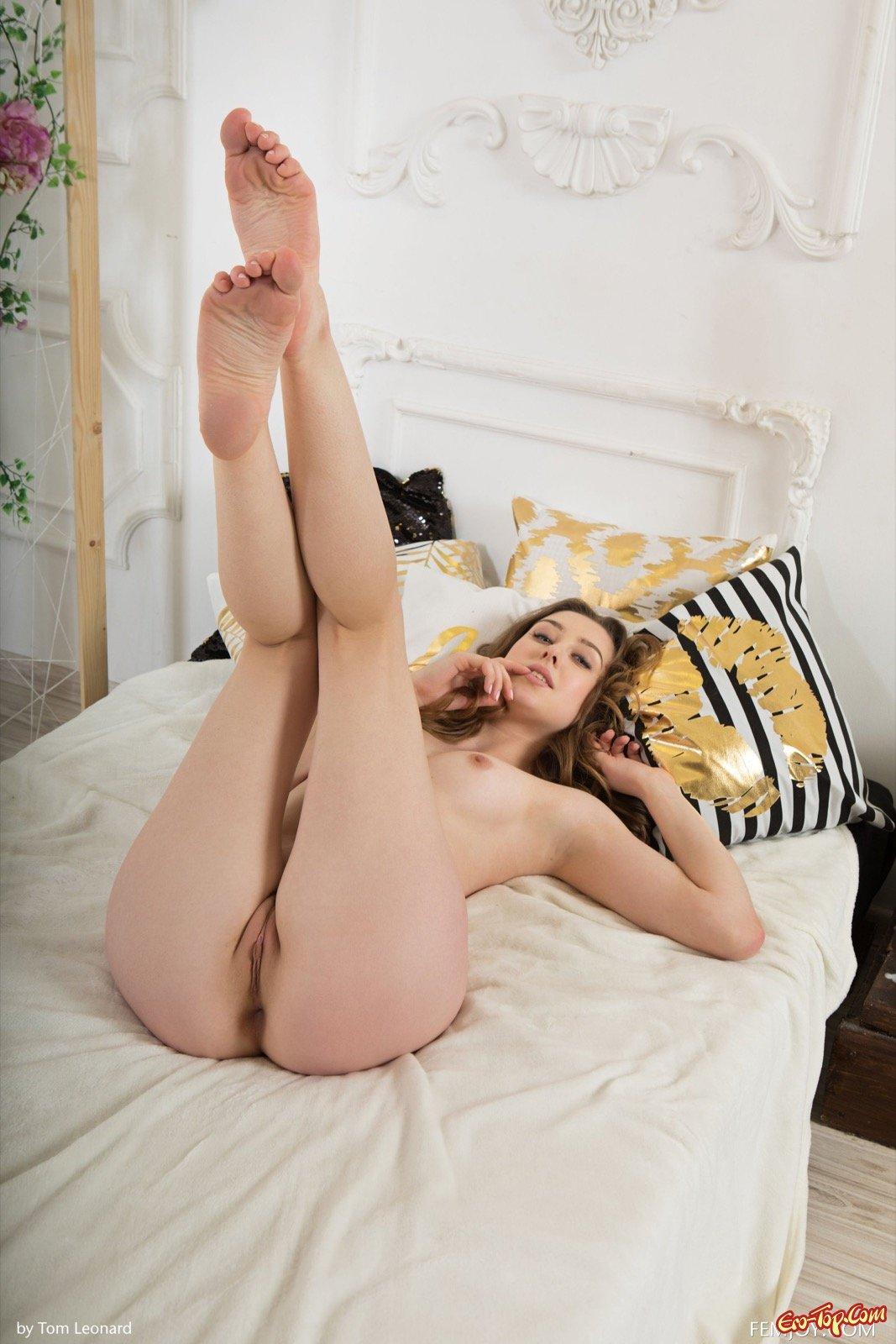 Голая девушка с волосатым лобком лежит в постели