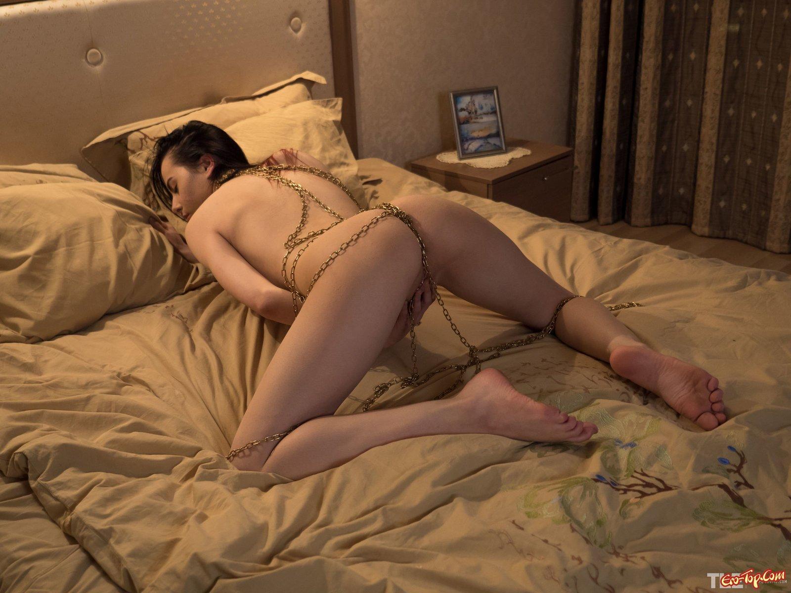 Голая сексуальная девушка в цепях позирует в постели