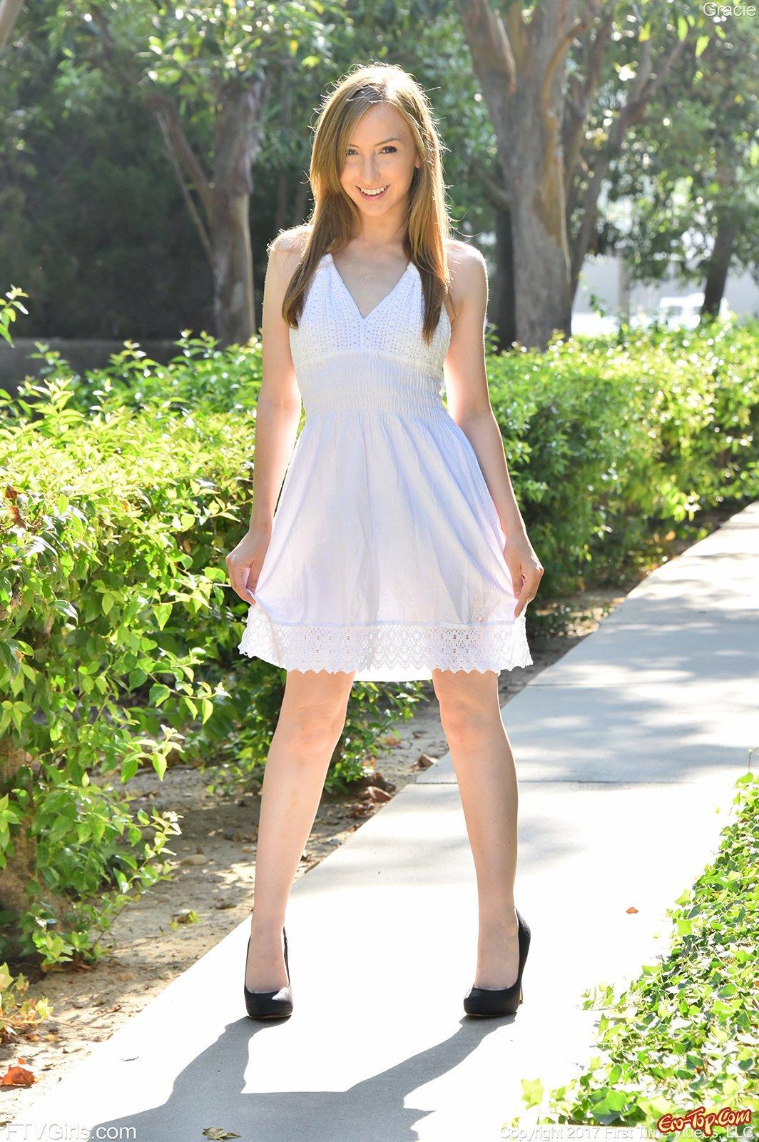 Стройная девушка снимает платье и позирует на улице