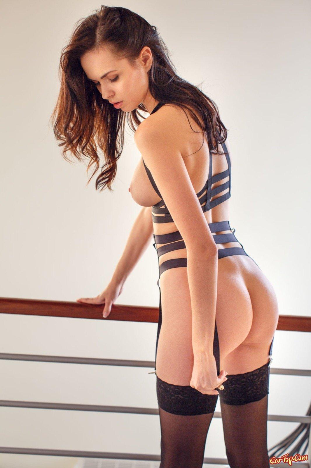 Девушка в чулках и на каблуках эротично позирует