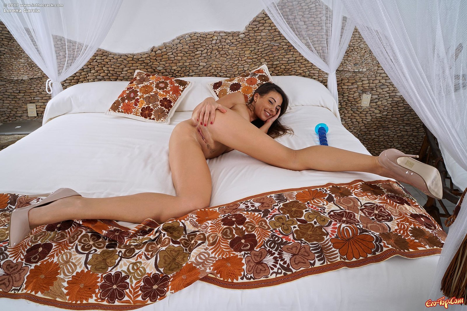 Загорелая девица оголившись позирует в постели