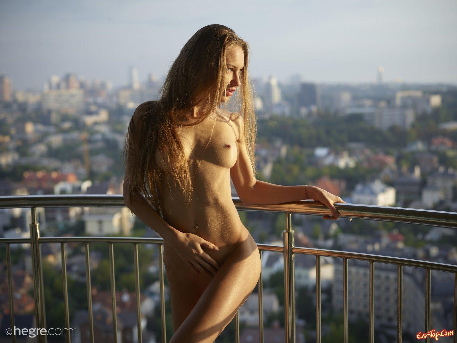 Голая красавица с красивыми ножками фотографируется на балконе