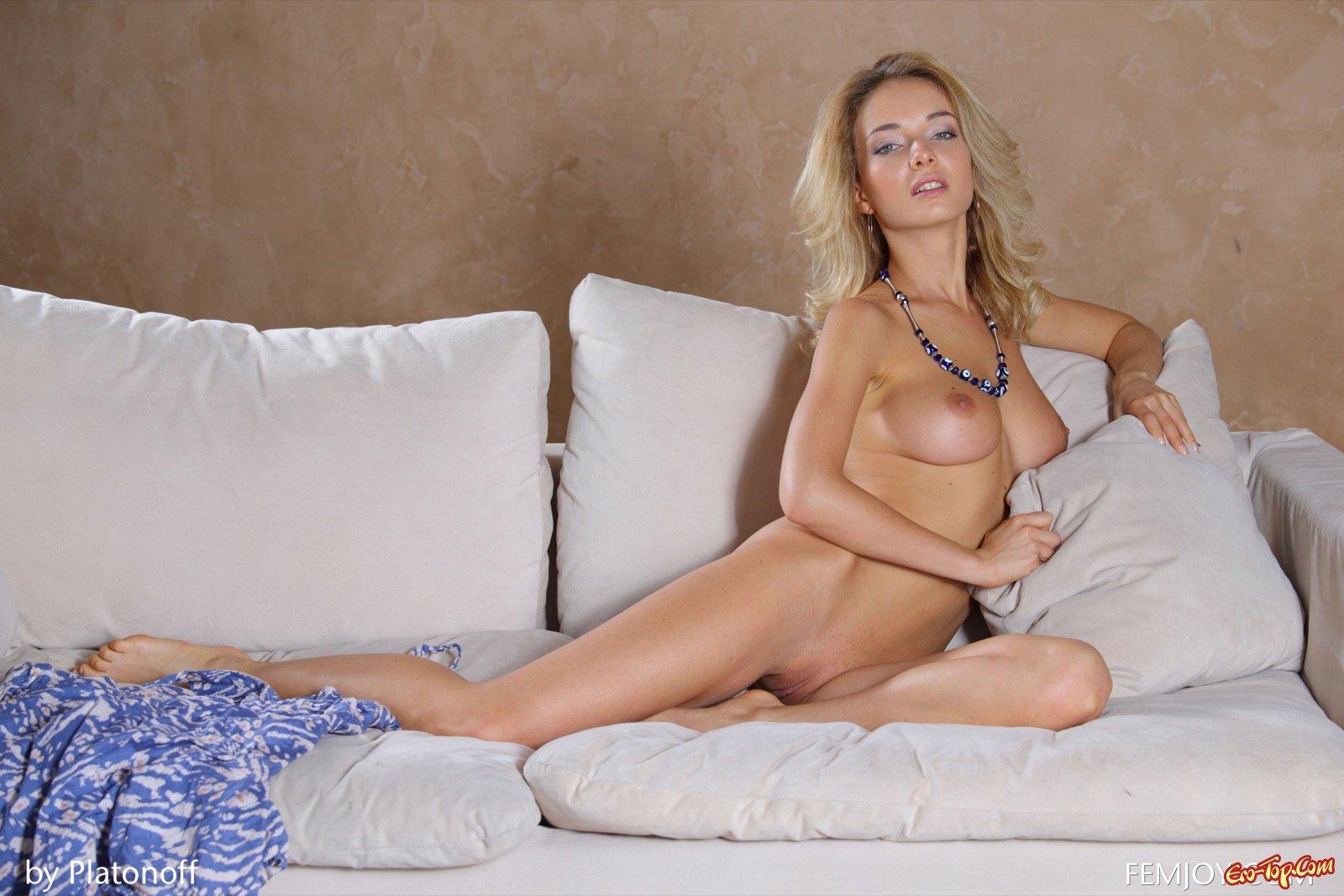 Милая блондинка обнажила стройные сиськи на диване