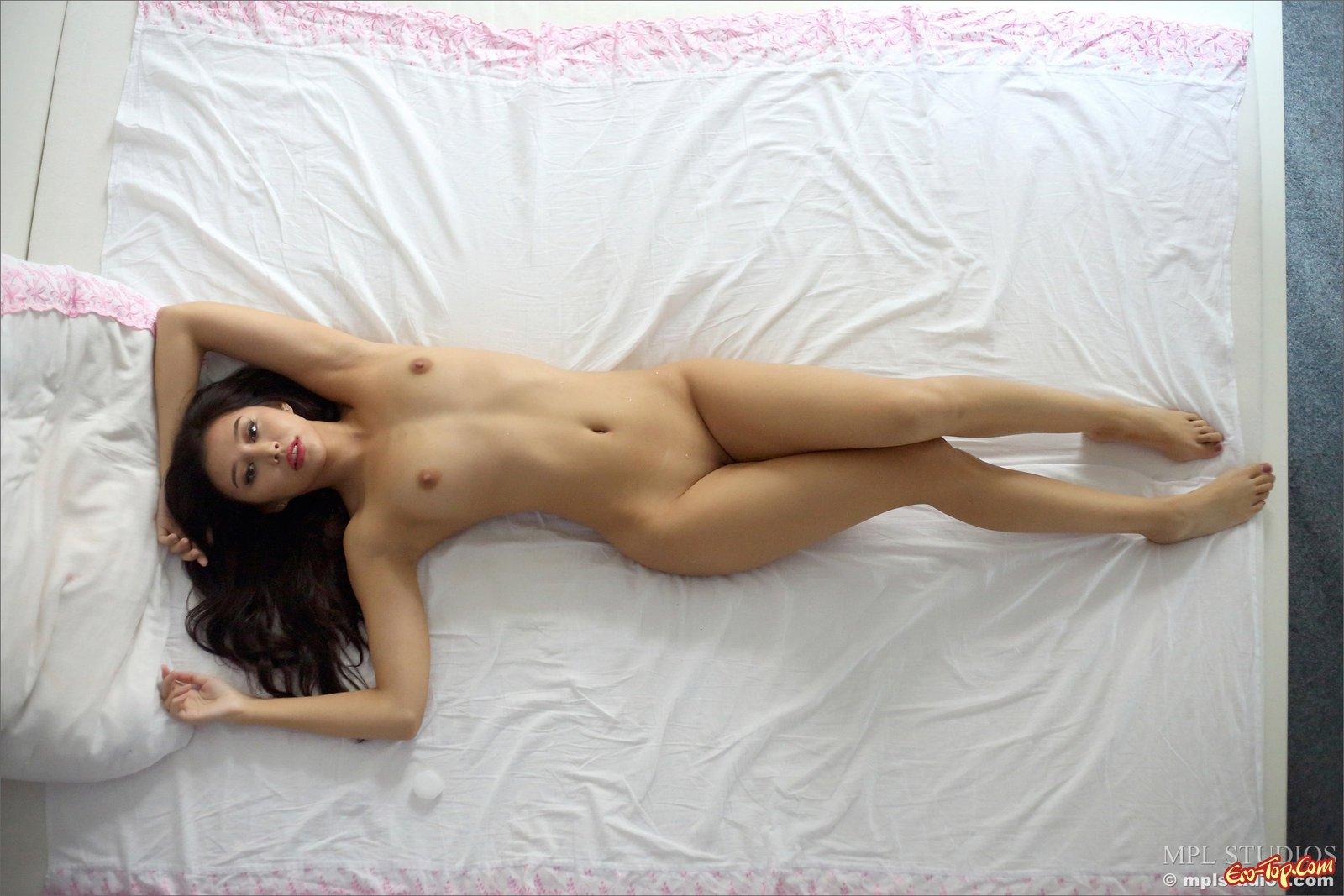 Возбуждающая красотка в колготках обнажилась на кроватке