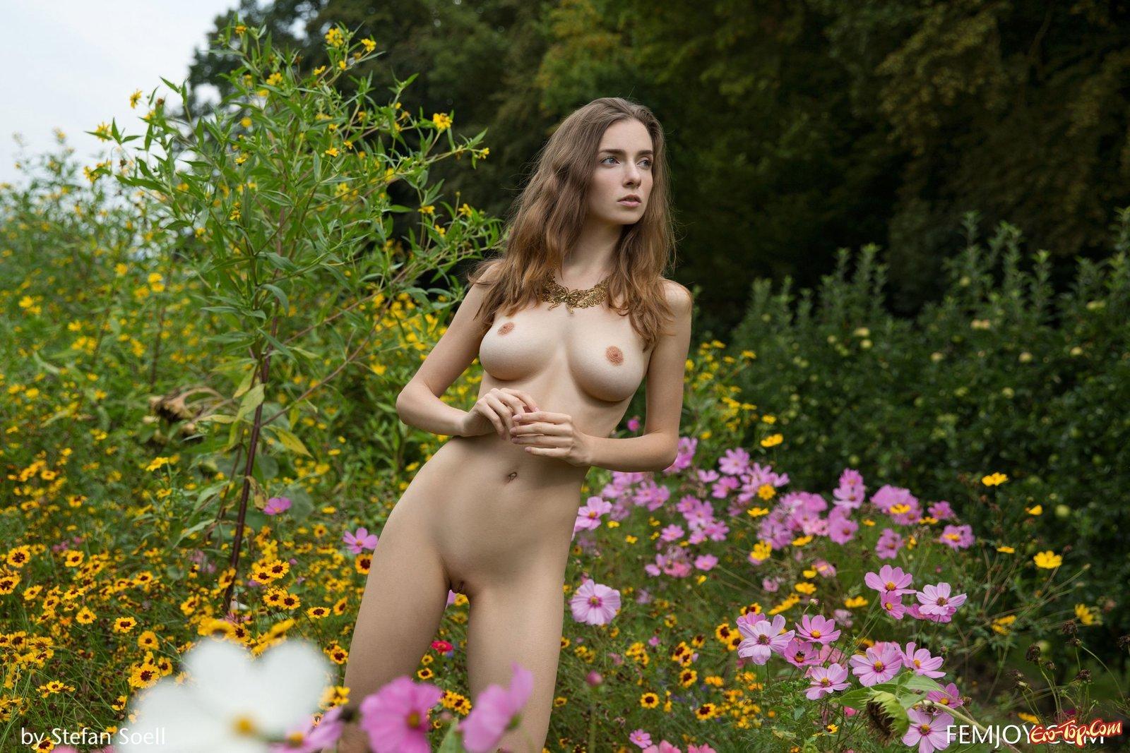 Раздетая красотка показала сиськи среди цветов