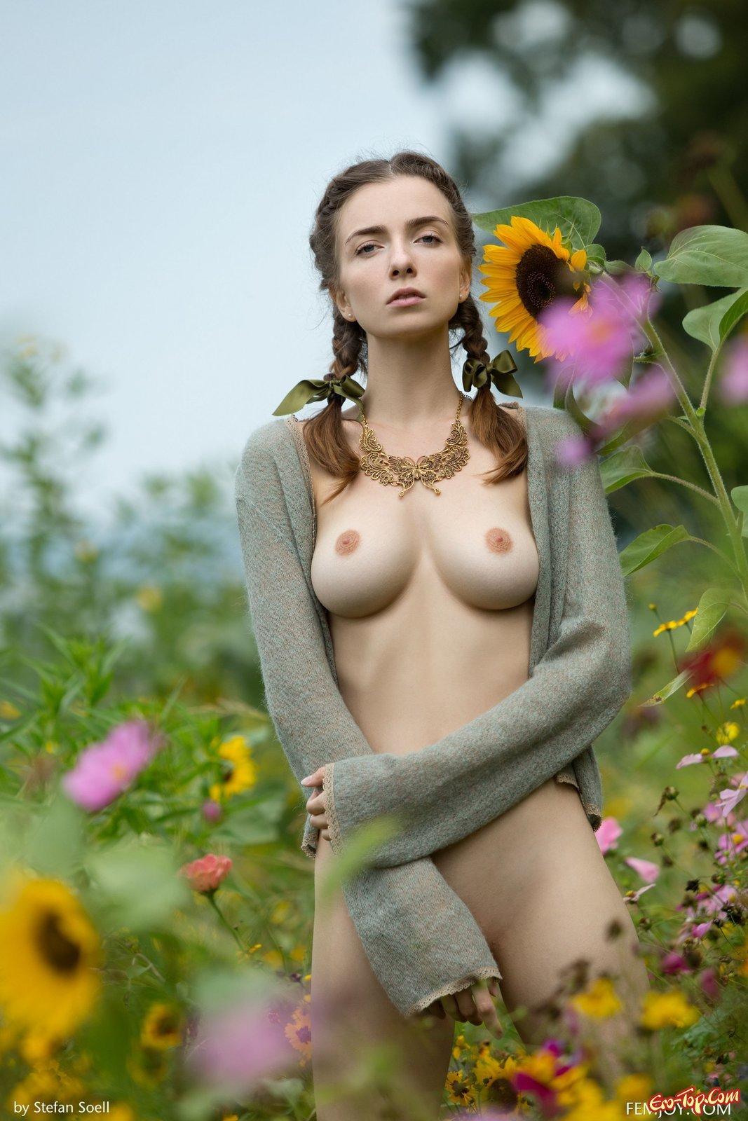 Голая красоточка показала титьки среди цветов смотреть эротику