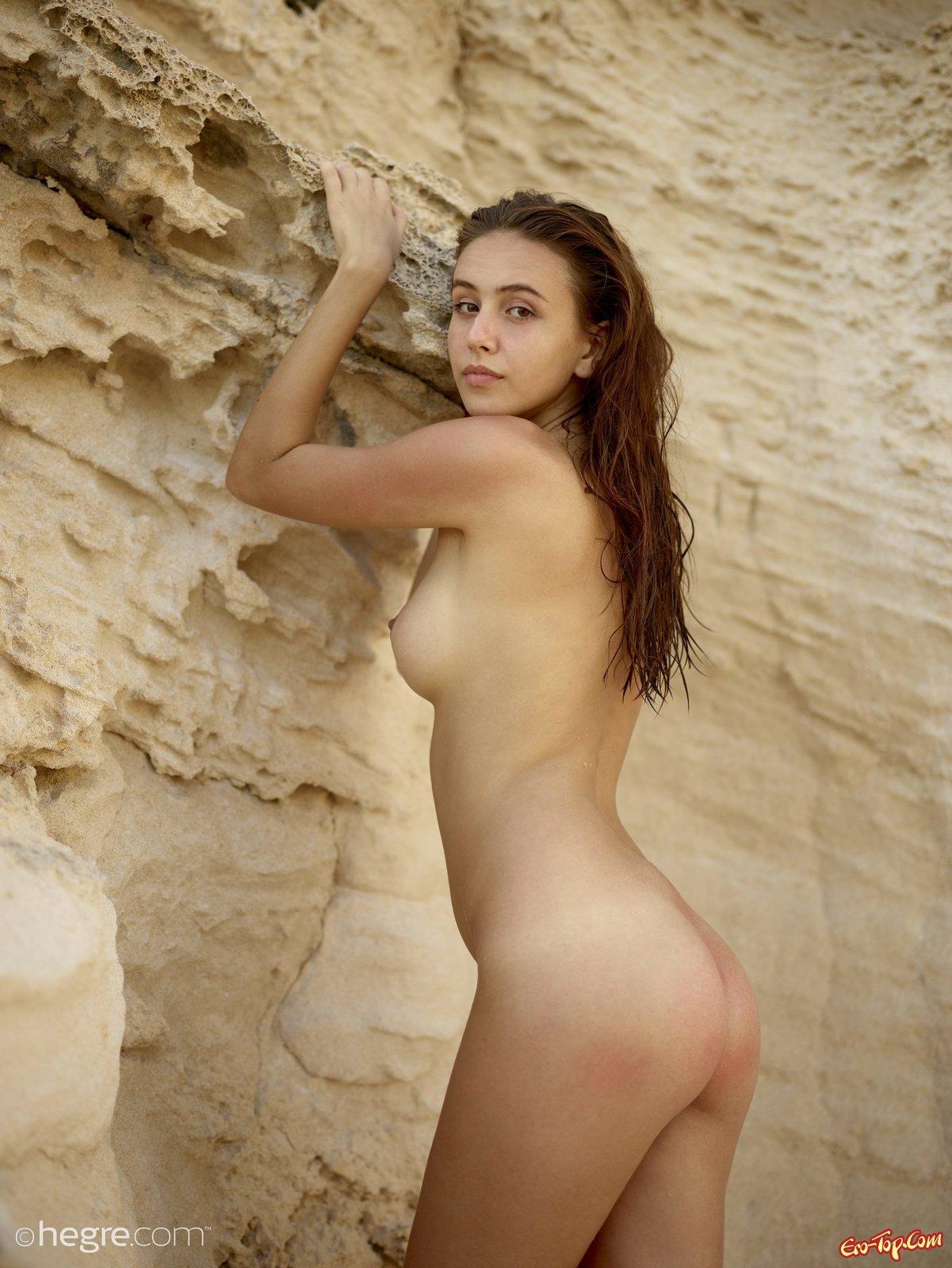 Путана с без бикини грудями и стриженной пиздой у скалы