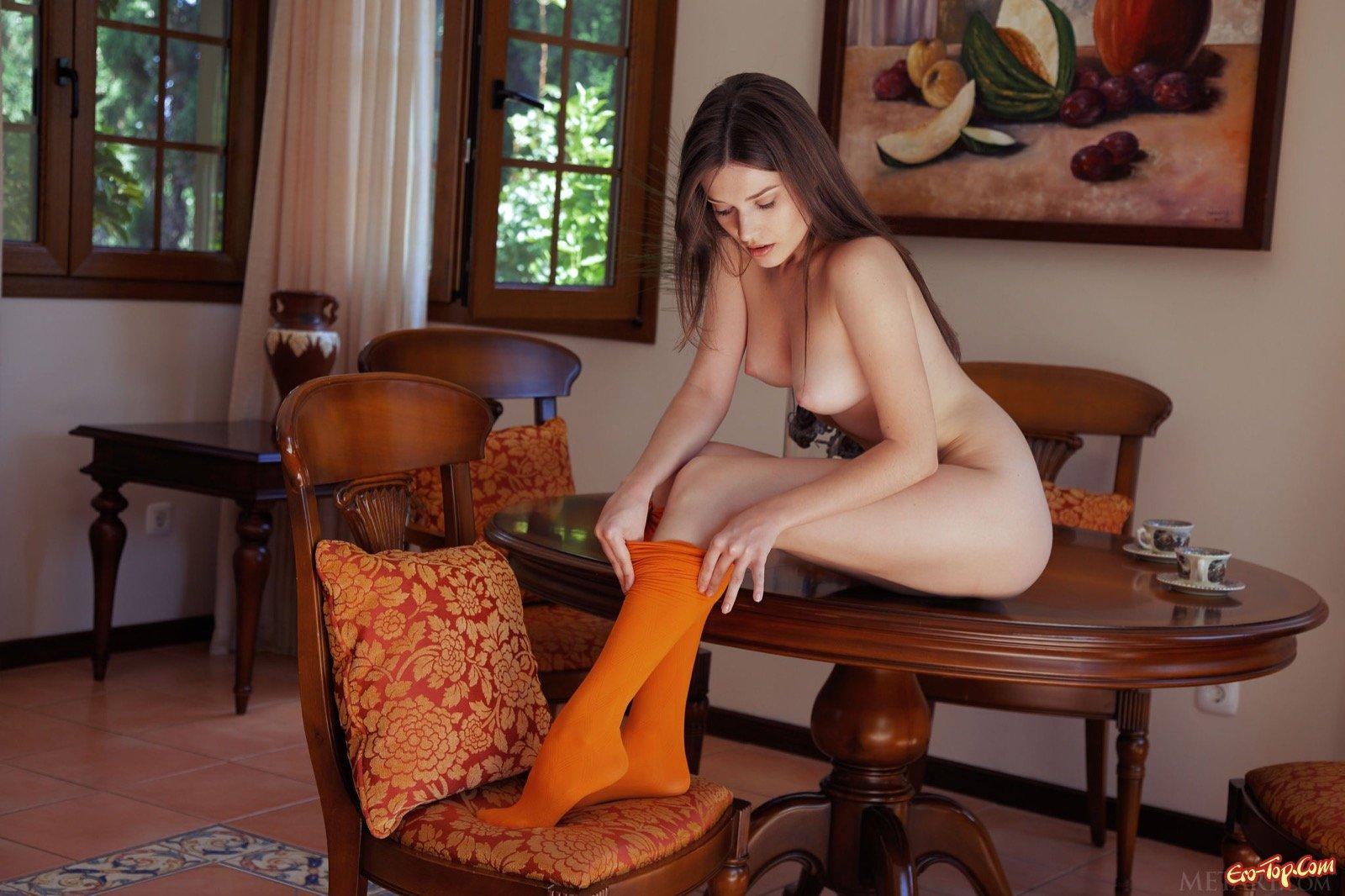 Стройная девица в колготках позирует на столе и полу