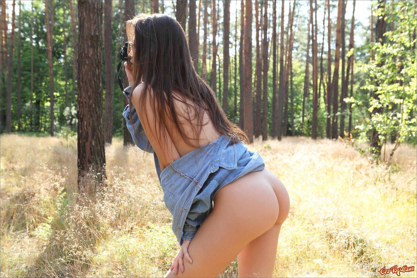 Шатенка в рубашке на голые сиськи красуется в лесу
