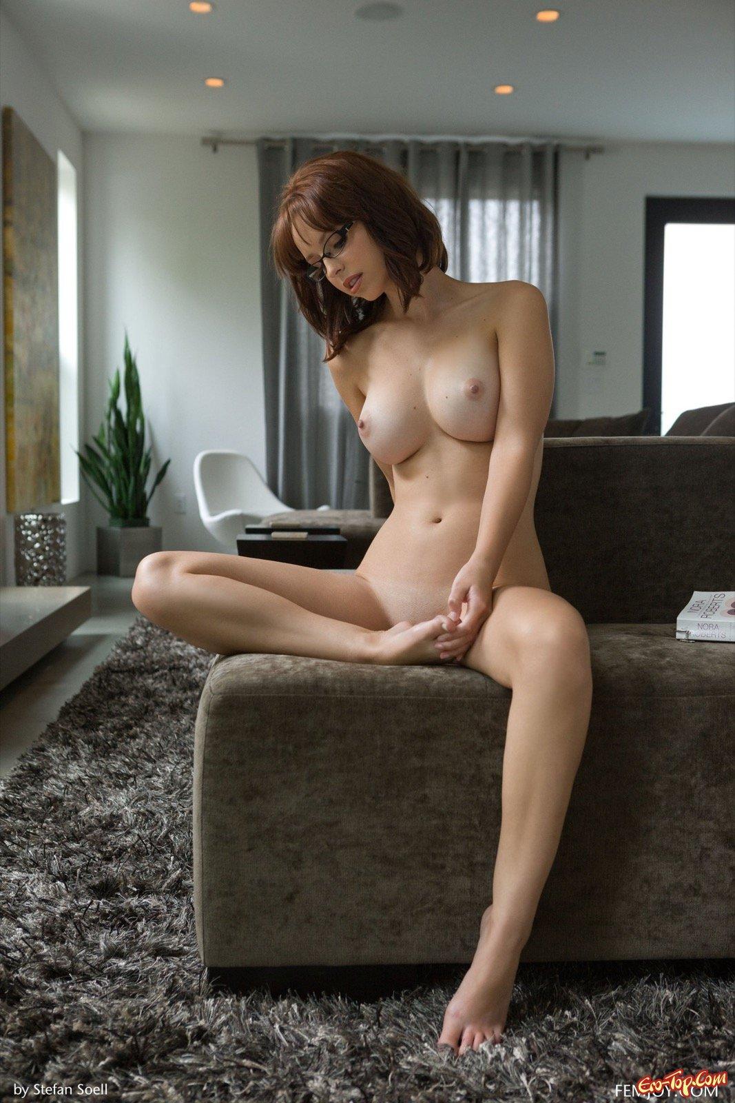 Шатенка с упругими титьками обнажилась сидя на диване