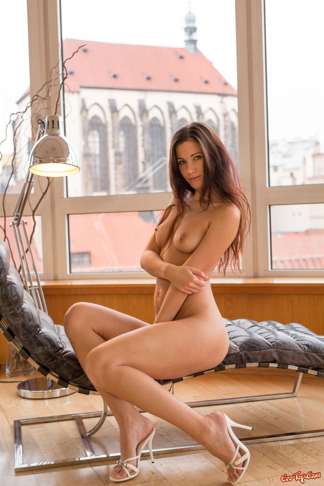 Стройняшка с красивой попой лежит на кушетке у окна
