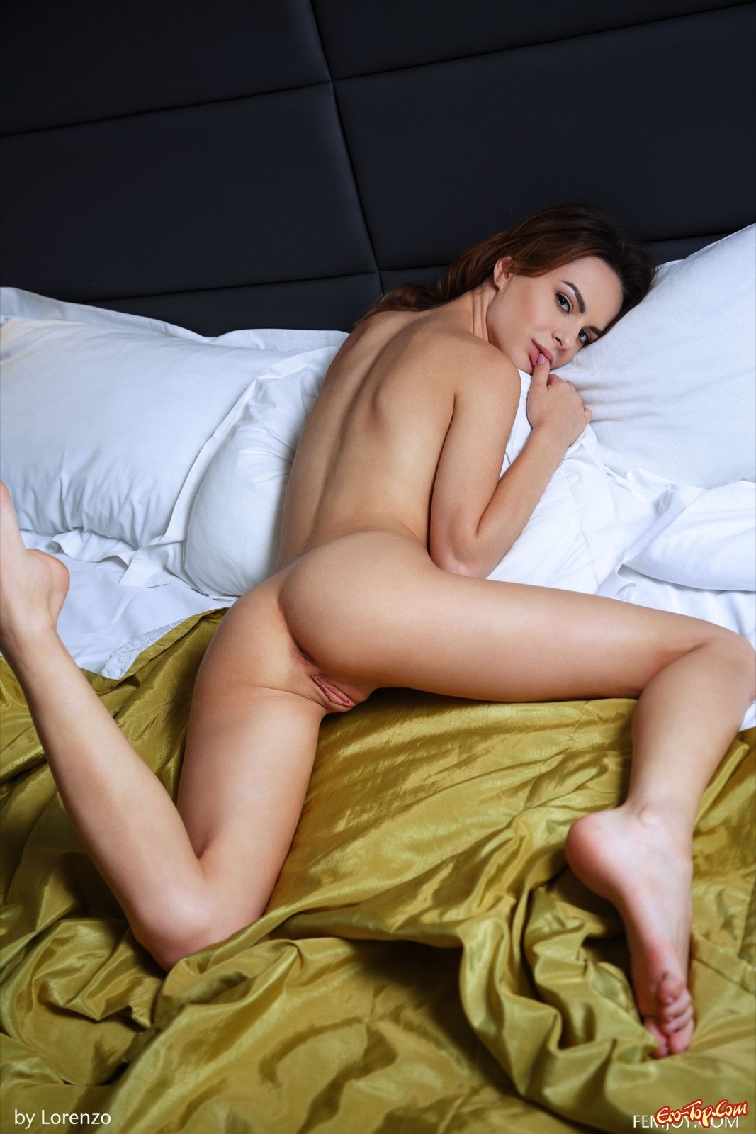 Голая девушка с красивыми глазами позирует в постели