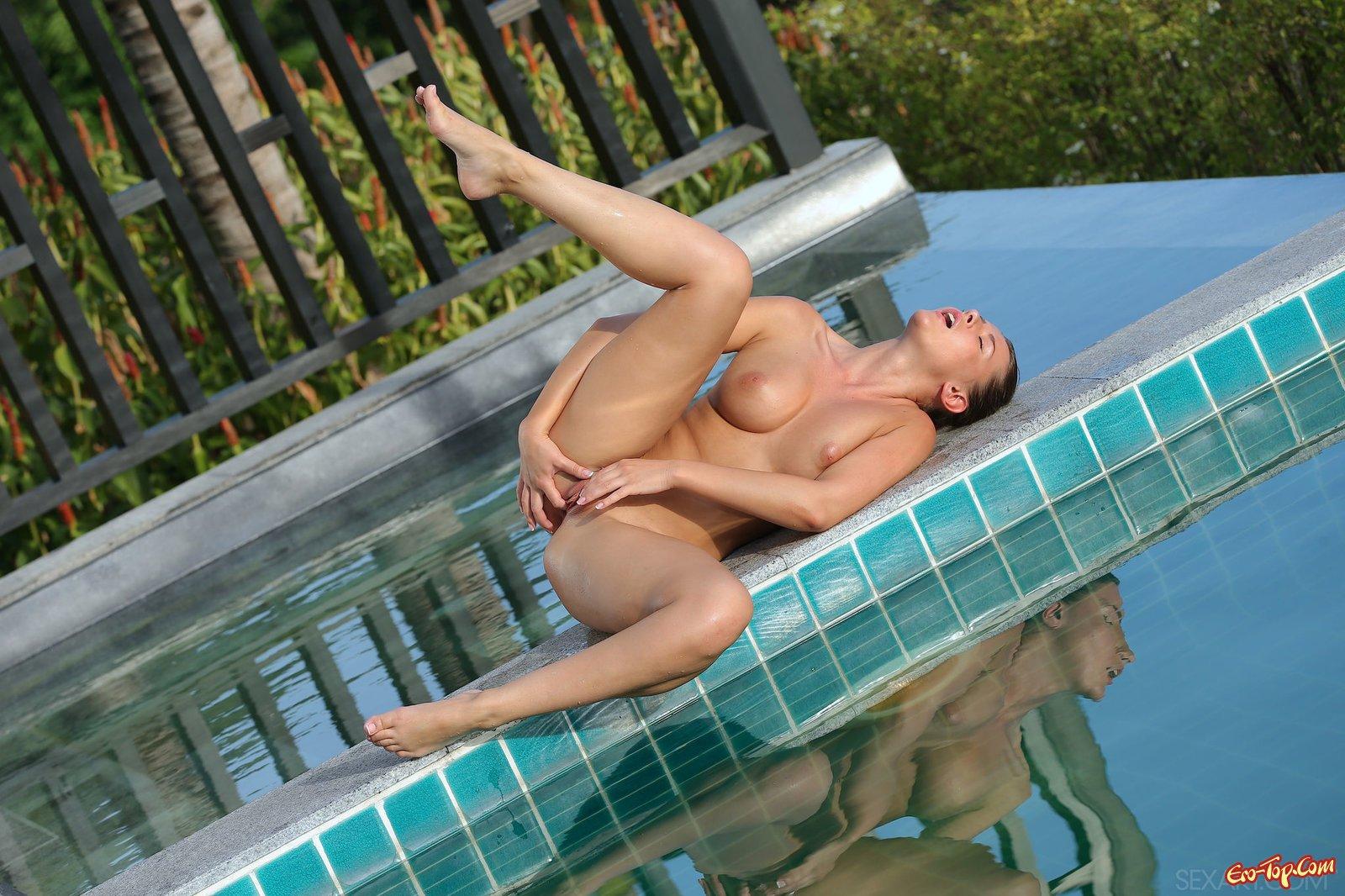 Стройная красавица ласкает обнаженное тело у бассейна