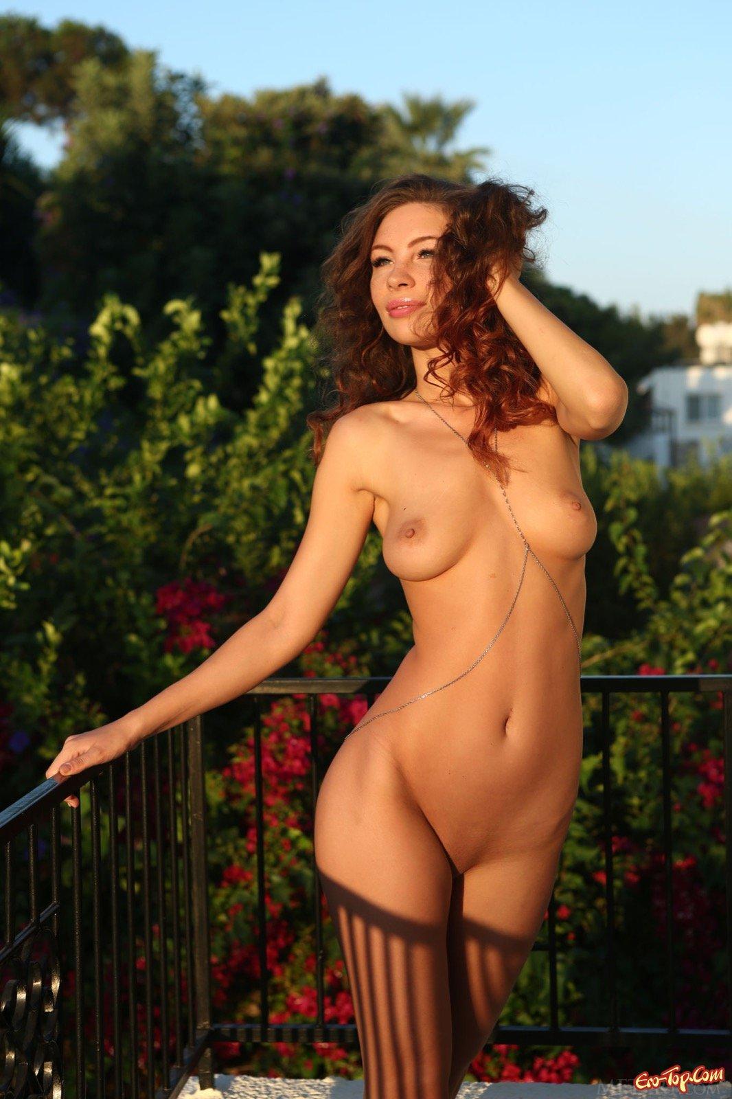Голенькая кудряшка страстно позирует на балкончике
