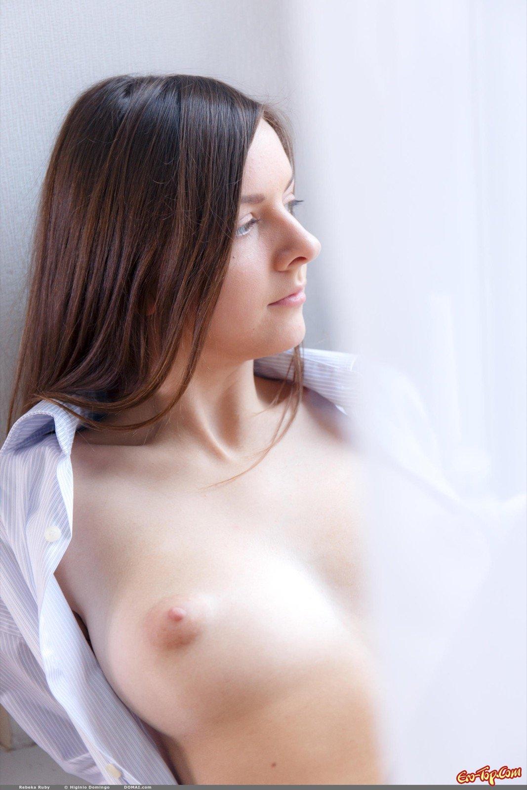 Нагая молоденькая woman в рубашке сидит рядом с окном