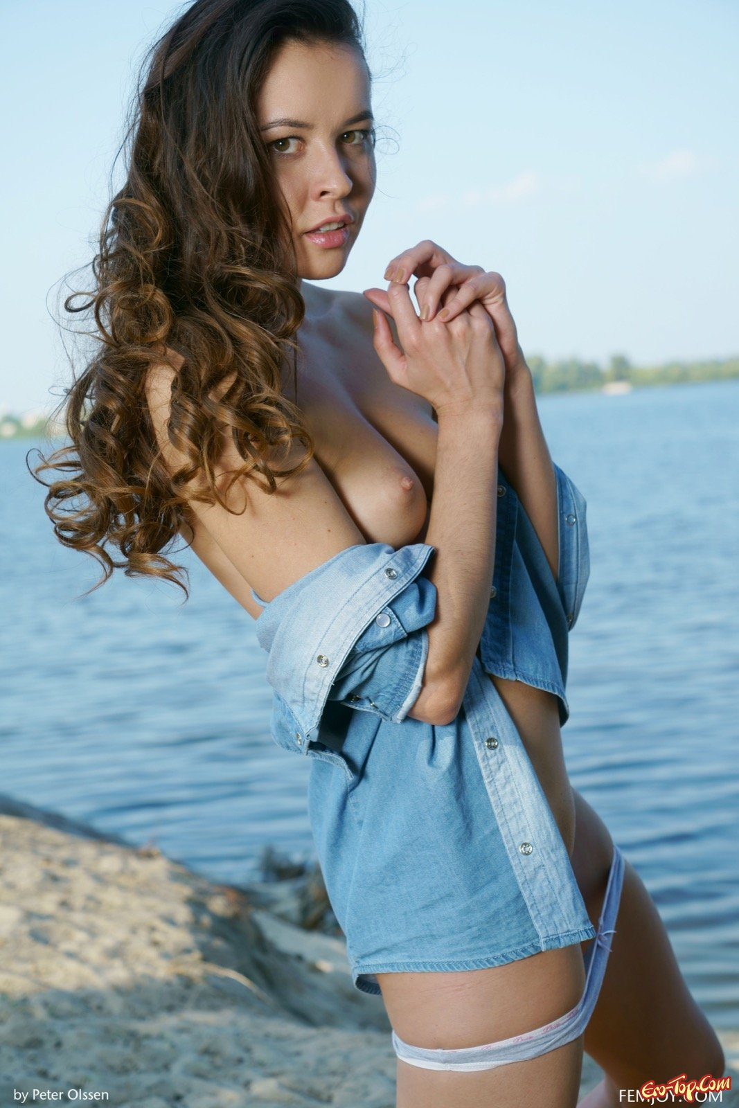 Девушка в рубашке снимает трусики на берегу речки