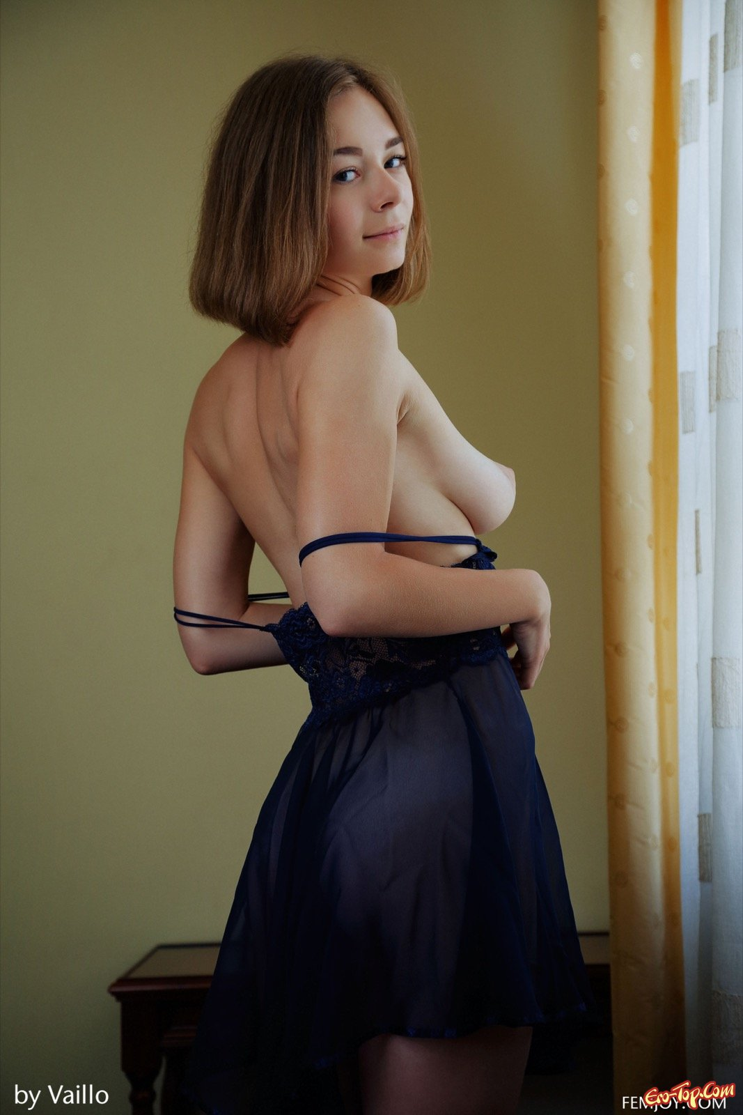 Девушка с каре показала висячие сиськи и киску у окна