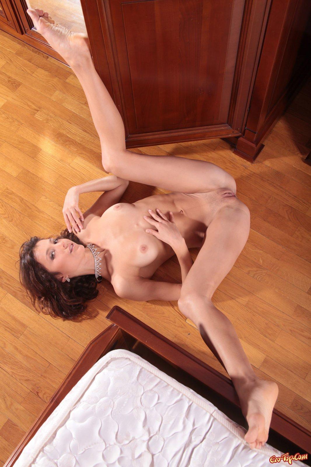 Худенькая шатенка показывает голое тело в спальне