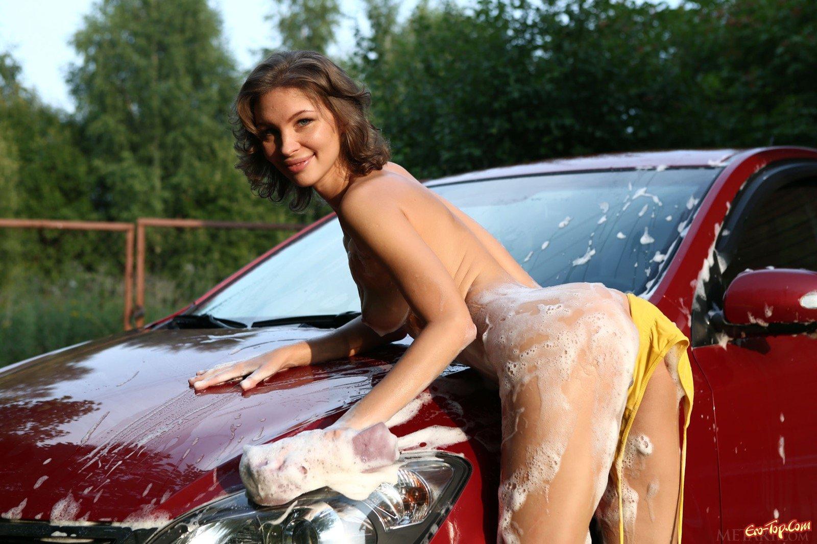 Голая девушка эротично моет машину обливаясь водой