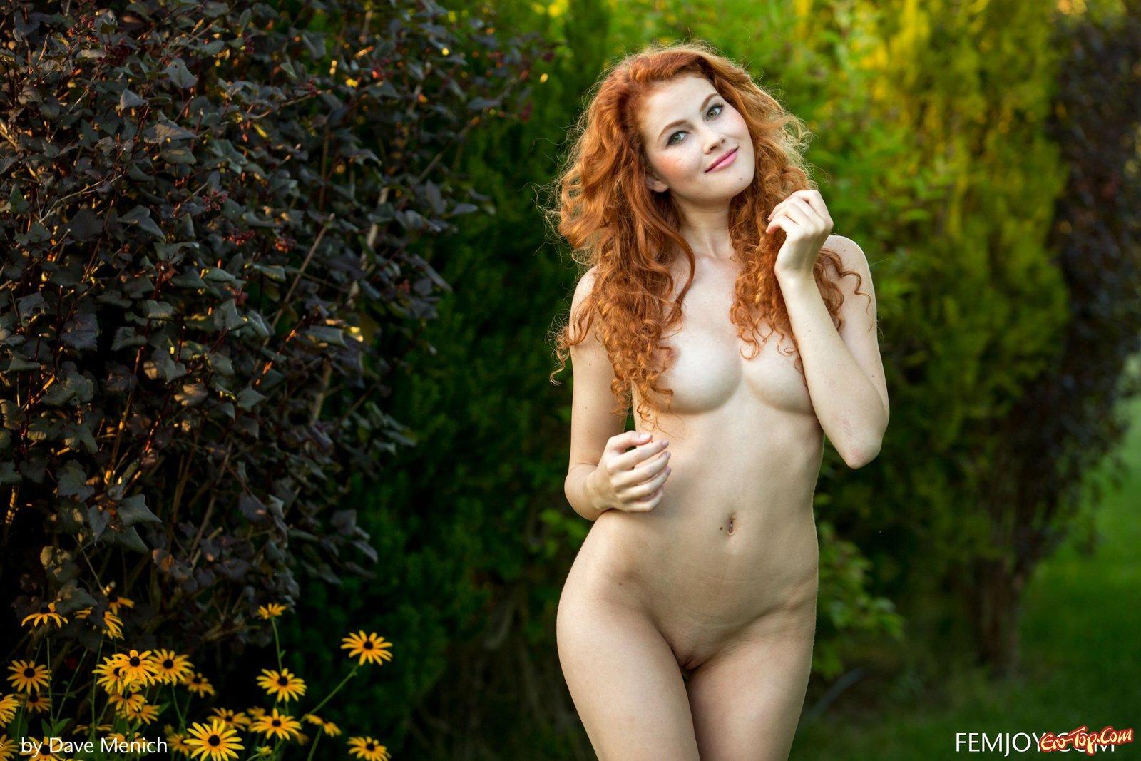Голая рыжеволосая девушка позирует на газоне