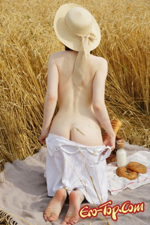 Рыжая девушка с косичками встала раком в поле