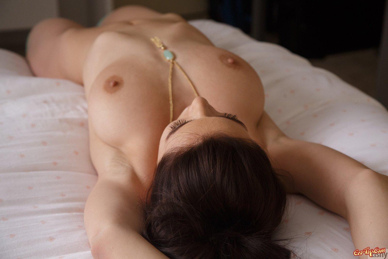 Красивая девка в вязаных чулках позирует в постели