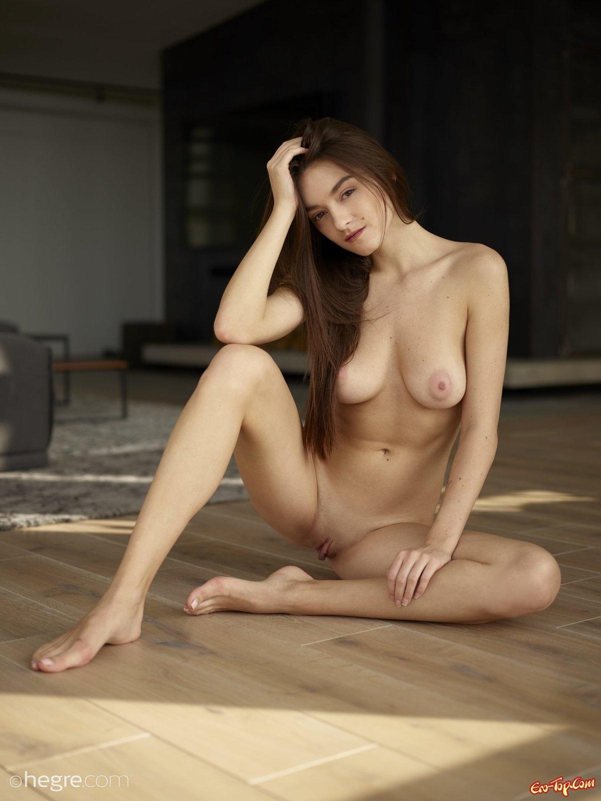 Шатенка с натуральной грудью раздвигает ноги на полу