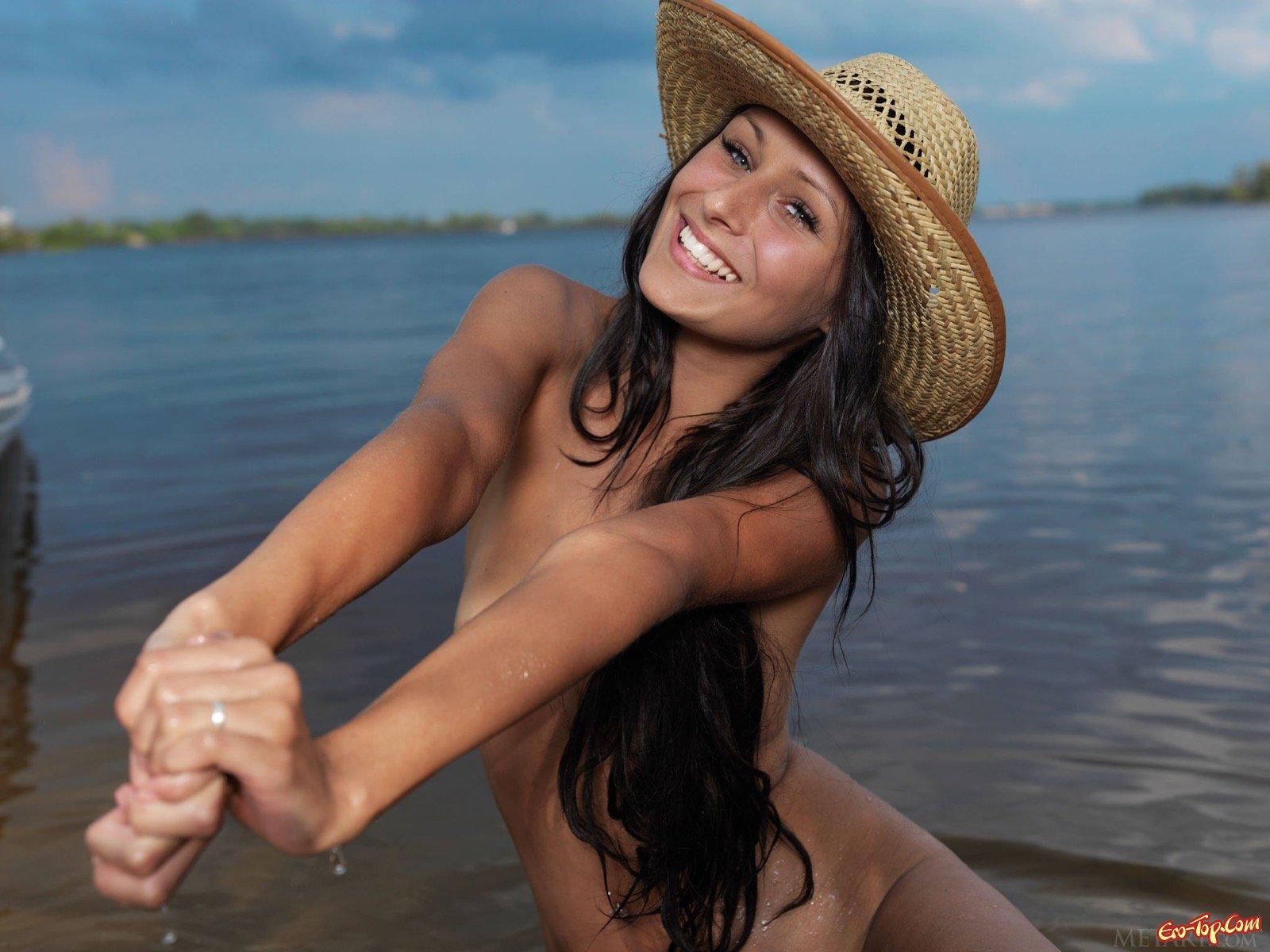 Раздетая девушка в шляпе намочила попку в речке