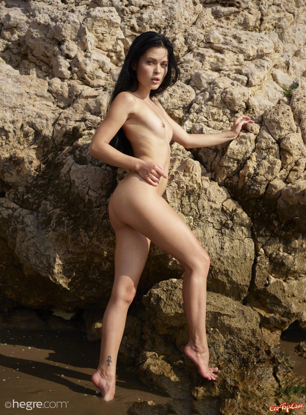 Голенькая брюнетка позирует на нудистском пляже