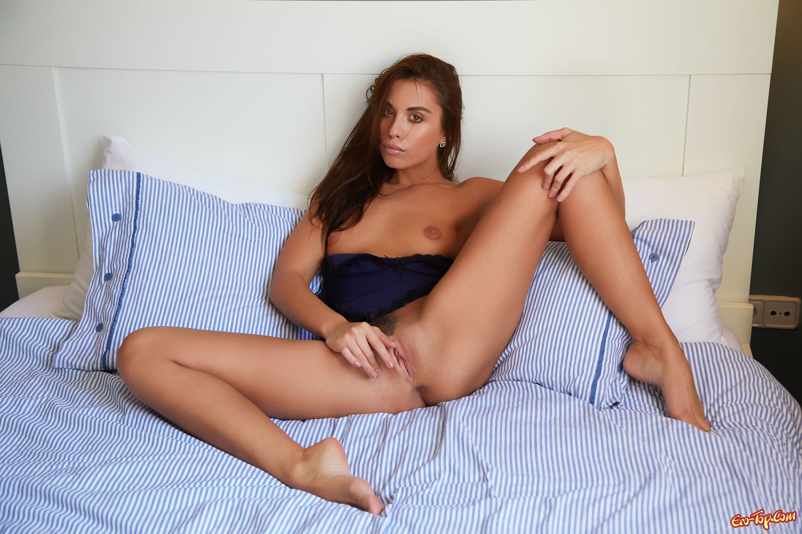 Шикарная девушка оголила бритую письку в постели