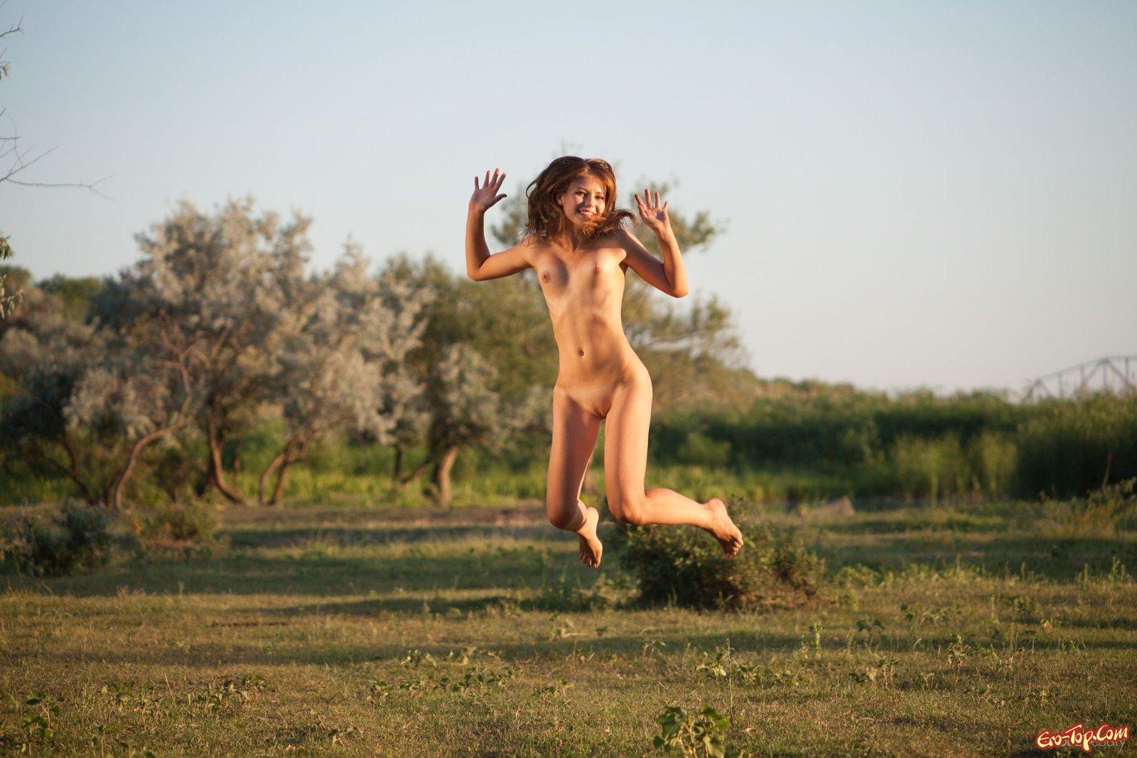 Голая темненькая девушка наслаждаясь позирует на природе