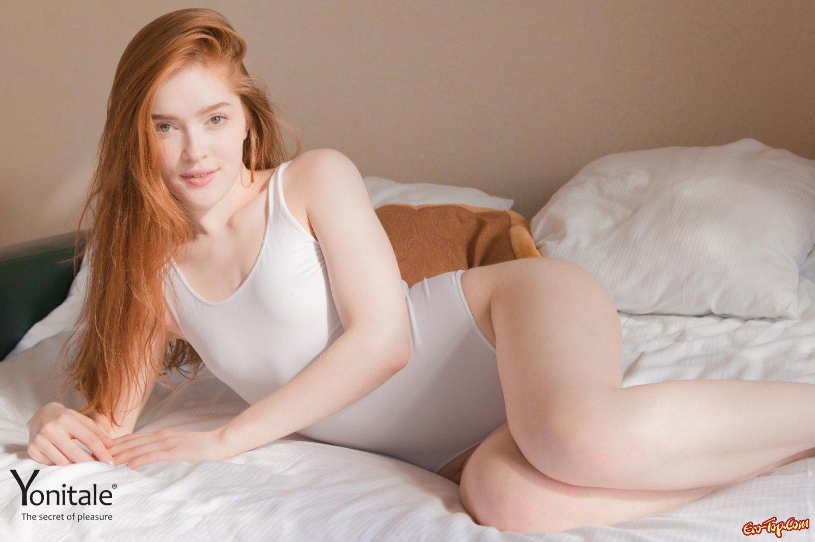 Рыжеволосая девушка сняла боди и делает селфи на кровати
