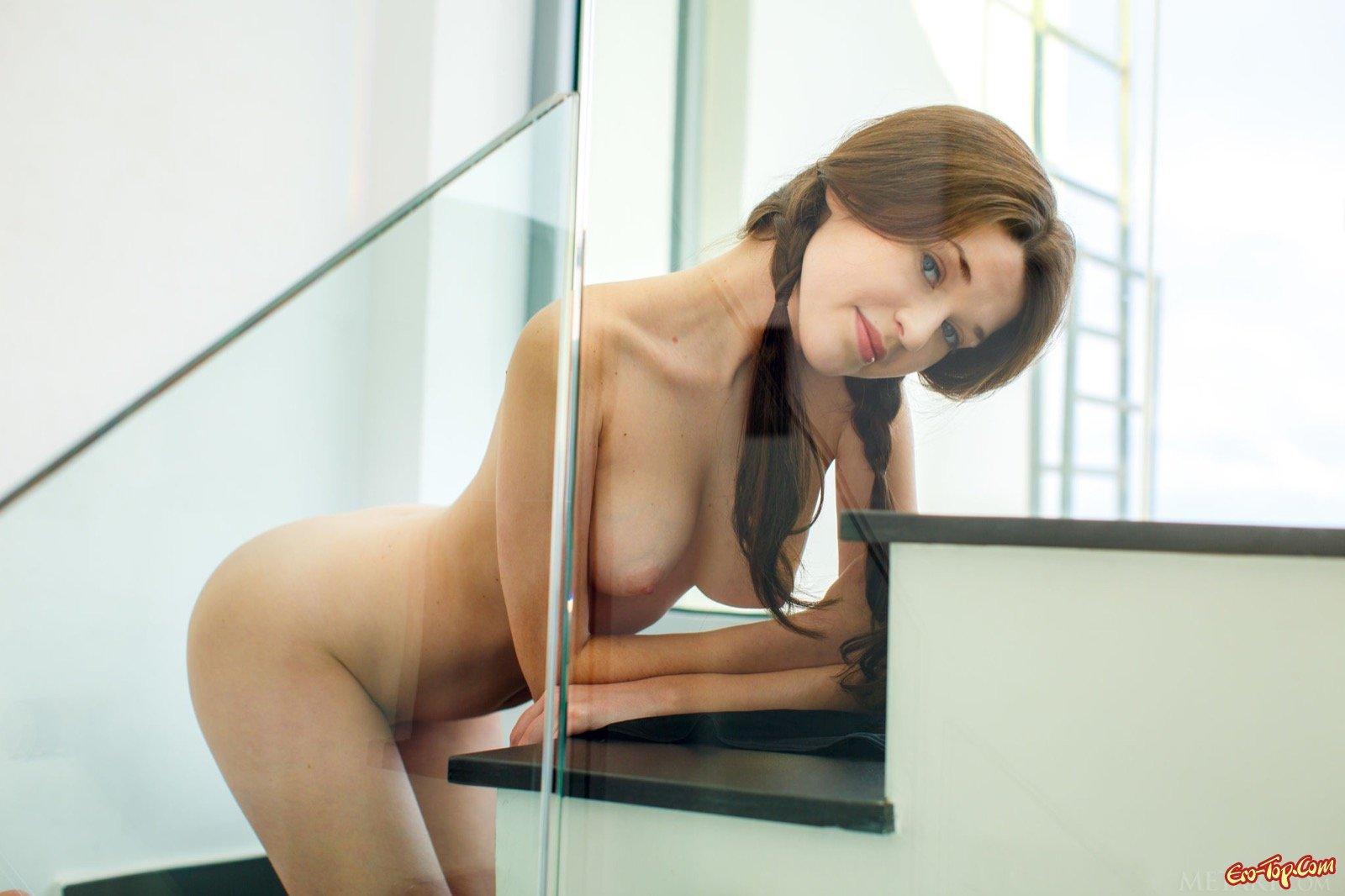 Молодая красавица эротично раздевается на лестнице