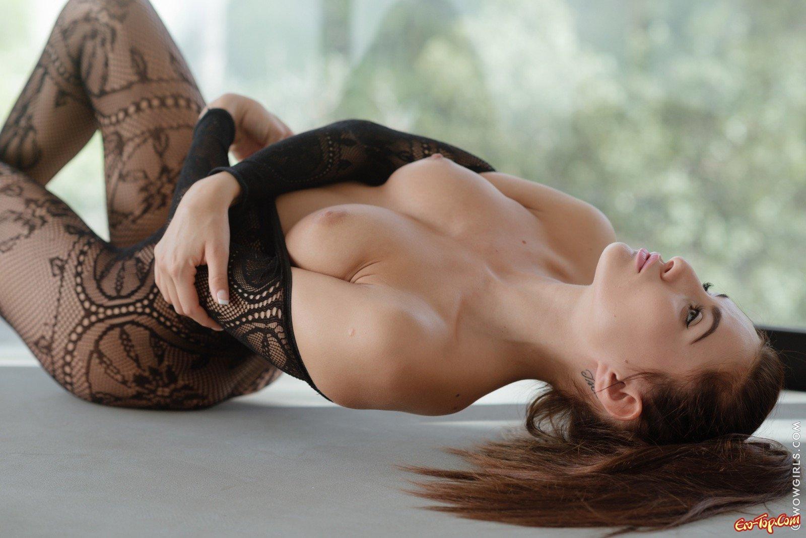 Гибкая девушка в секс комбинезоне позирует на полу