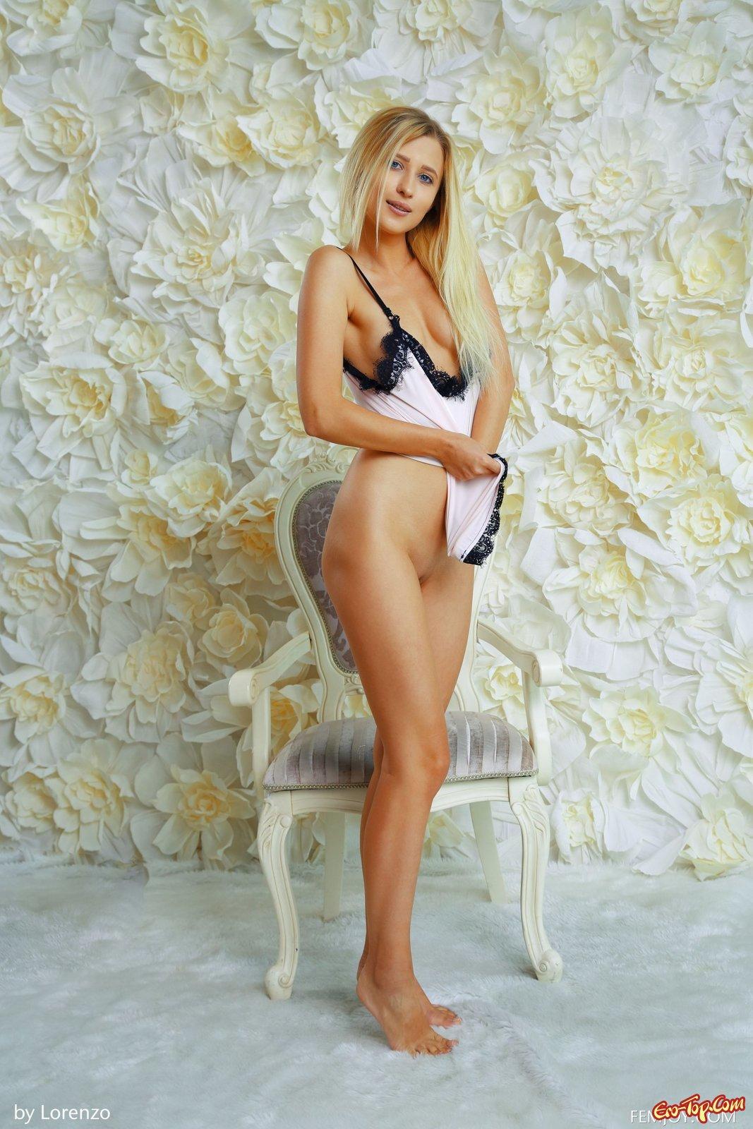 Голубоглазая блондинка с маленькой грудью на стуле
