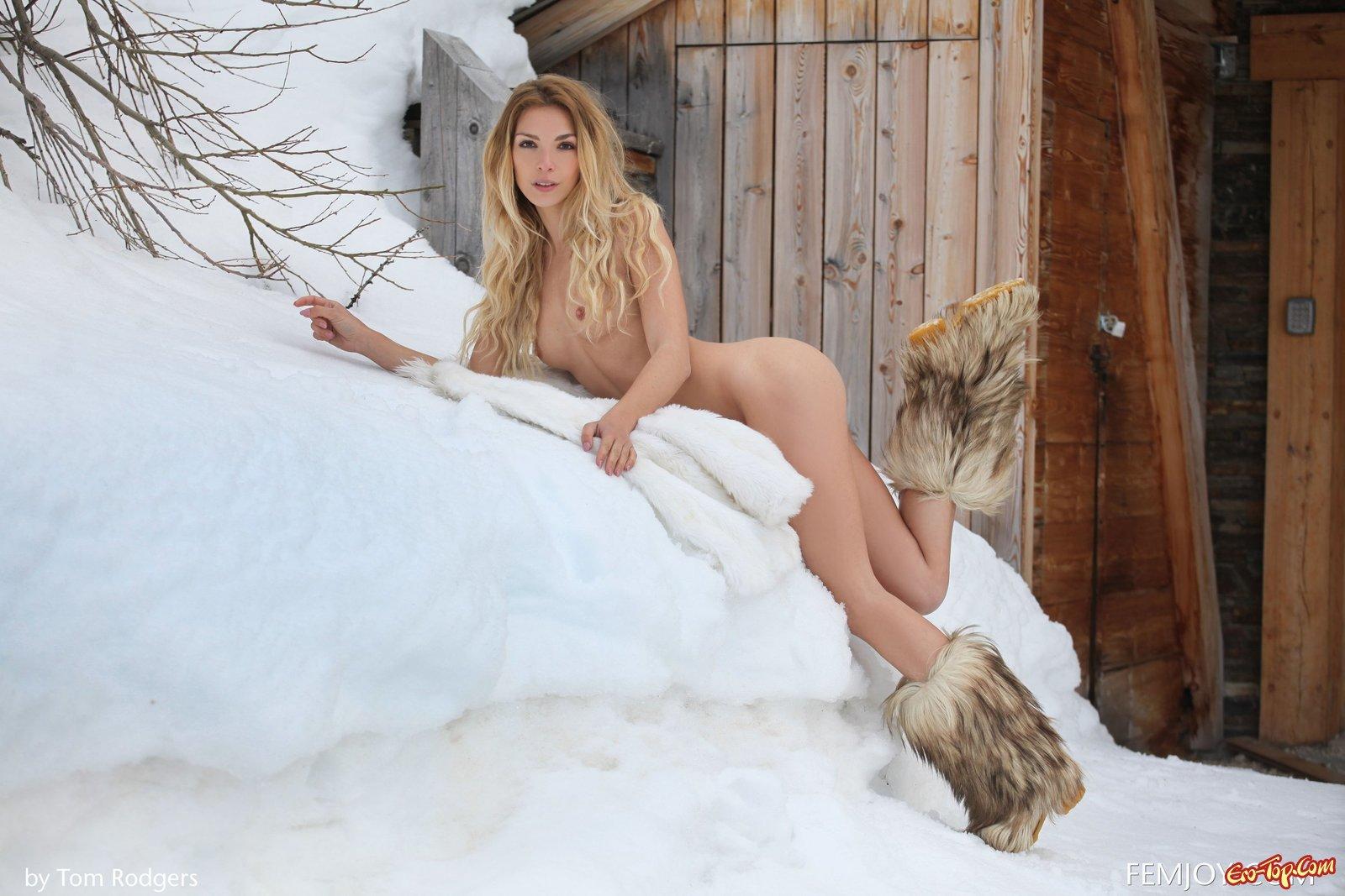 Голая блондинка в шубе позирует на снегу
