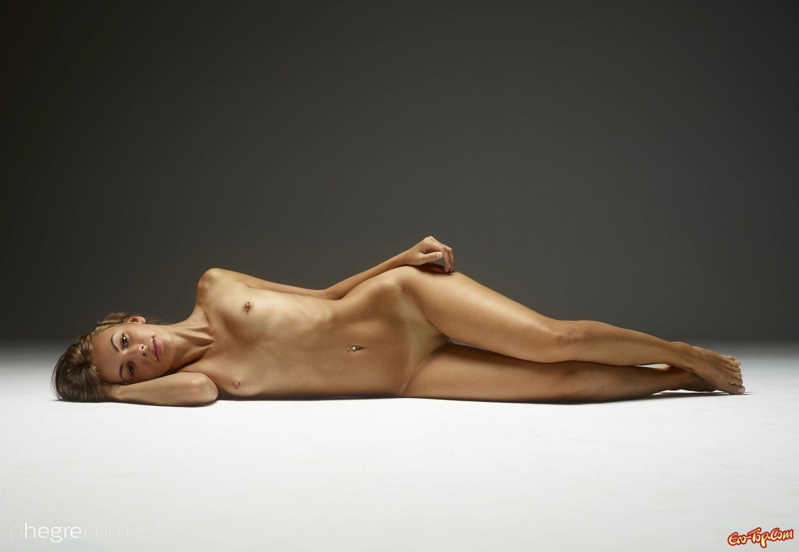Симпатичная худощавая модель валяется голой на полу